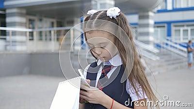 La escuela primaria con uniforme, centrada en los estudiantes, escribe o dibuja algo en un cuaderno cerca del edificio escolar almacen de video