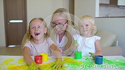 La famiglia felice dipinge i colori La famiglia felice dipinge i colori La madre e la figlia divertendosi e si dipingono ` s sui  archivi video
