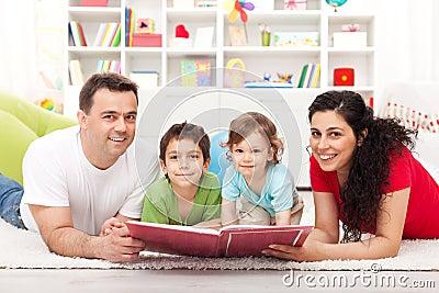 La familia joven con dos cabritos que leen una historia reserva