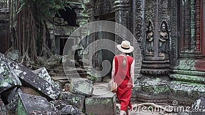 La femme caucasienne dans la robe rouge marche parmi des ruines des ventres Prohm banque de vidéos