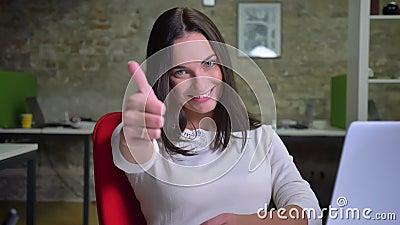 La femme d'affaires dans le bureau observe à la caméra et met son doigt jusqu'à l'exposition semblables et au respect clips vidéos
