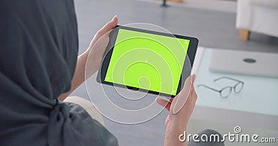 La femme d'affaires musulmane dans le hijab allume l'appli sur le comprimé horizontal avec l'écran et les montres verts de chroma banque de vidéos
