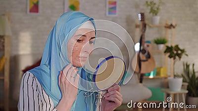 La femme musulmane dans un hijab regarde dans le miroir sa cicatrice d'une brûlure sur son visage et cris banque de vidéos