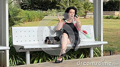 La femme se bichonne appeler par le téléphone portable banque de vidéos