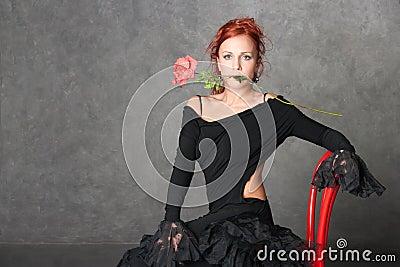 La fille avec du charme avec une rose rouge