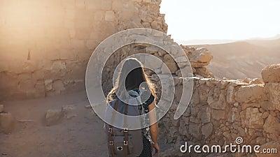 La fille avec le sac à dos explore des ruines antiques de désert La jolie femme marche parmi des murs de forteresse de montagne d banque de vidéos
