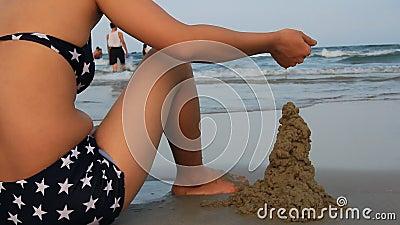 la fille a construit un château de sable sur la plage banque de vidéos