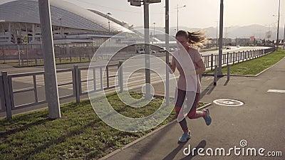 La fille court Arène du football de mouvement lent du parc olympique dans la ville de Sotchi banque de vidéos