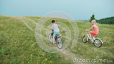 La fille et le garçon ont l'amusement montant vers le haut de la colline sur des bicyclettes Concurrencez qui escalade d'abord la clips vidéos