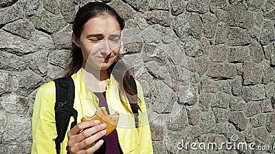La fille a les hoquets tout en mangeant ?motions dr?les Un casse-croûte rapide avec un petit pain d'hamburger sur la rue Viande s banque de vidéos