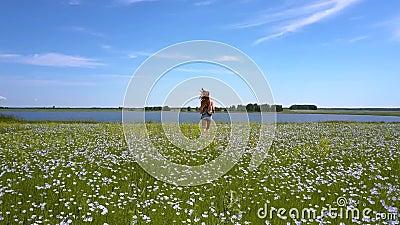 La fille mince court sur le gisement de sarrasin au lac éloigné banque de vidéos