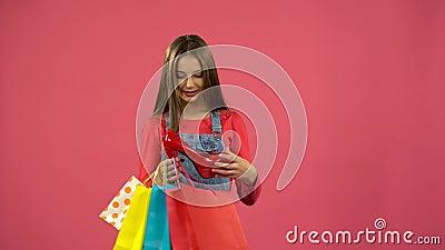 La fille obtient une chaussure rouge du sac et est heureuse Fond rose banque de vidéos