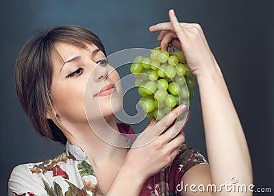 La fille regarde sur des raisins