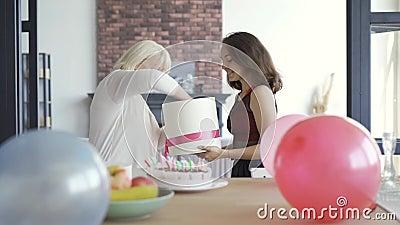 La fille souhaite à maman un joyeux anniversaire et lui donne sa boîte de cadeau avec de la lingerie dedans Les femmes qui s'embr clips vidéos