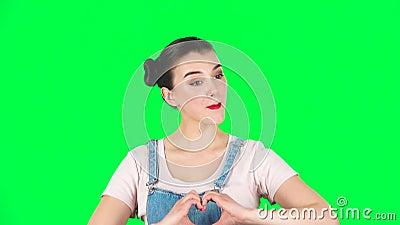 La fille sourit doucement et montre son coeur avec les doigts, puis baiser, ralenti clips vidéos