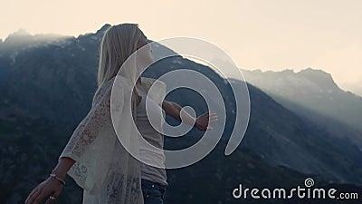 La fille sportive danse sur le dessus du monde, des belles montagnes et du ciel bleu sur l'horizon Elle essaye à banque de vidéos