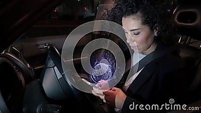 La fille touche l'écran tactile olographe de navigation du téléphone portable tout en se reposant derrière le volant clips vidéos