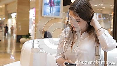 La fille utilise le téléphone dans le mail se reposant sur un banc banque de vidéos