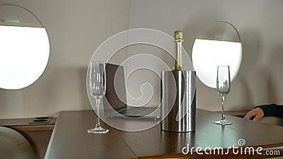 La gérance apporte du champagne à l'entrepreneur à l'intérieur du jet privé clips vidéos