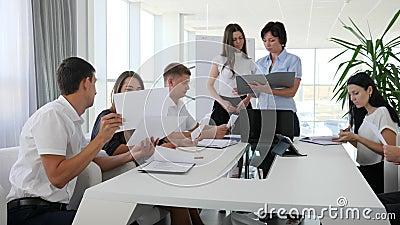 La gente de la oficina con los documentos a disposición habla en la reunión en la sala de reunión moderna en centro de negocios almacen de metraje de vídeo