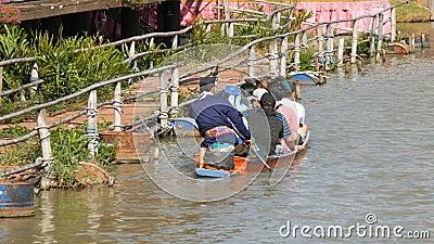 La gente sta nuotando in una barca su un fiume marrone in Tailandia Guidando sul fiume in una barca Mercato di galleggiamento di  video d archivio