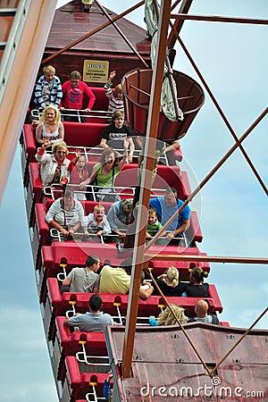 La gente sulla nave d oscillazione sotto il cielo nuvoloso blu Immagine Editoriale