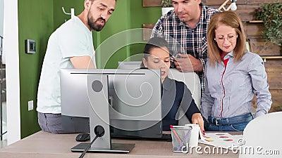 La giovane azienda Ceo è seduta su una scrivania ad aiutare i suoi datori di lavoro con le sue conoscenze video d archivio