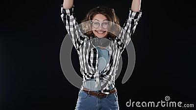 La giovane bellissima donna ricciola con le cuffie sul collo salta sorprendentemente nel telaio, appare sullo schermo Sorriso stock footage