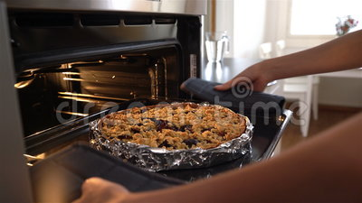 La giovane casalinga attraente esce della torta calda deliziosa del forno carrello archivi video