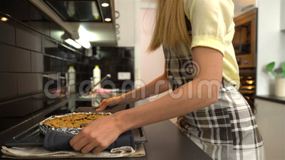 La giovane casalinga attraente esce della torta calda deliziosa del forno carrello video d archivio
