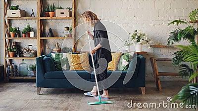 La giovane donna attraente sta pulendo il salone che passa lo straccio sul pavimento che fa il lavoro domestico Bello appartament archivi video