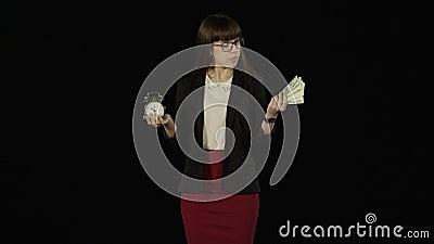 La giovane donna graziosa tiene le sue mani su come scale con un orologio ed i soldi in  video d archivio