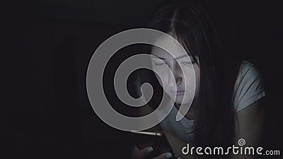 La giovane donna nello scuro alla notte si siede con un telefono nelle reti sociali stock footage