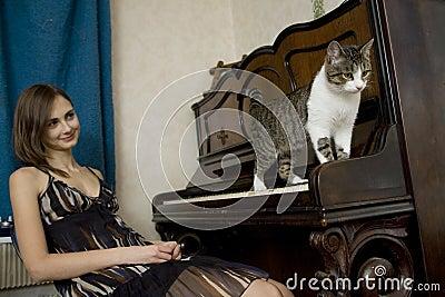 La giovane donna sta guardando il gatto camminare sul piano