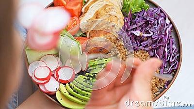 La giovane donna sta mangiando un'insalatiera sana
