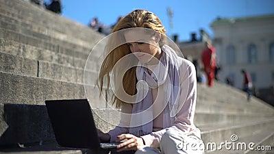 La giovane donna utilizza un computer portatile sulle scale nel centro della città Movimento lento archivi video