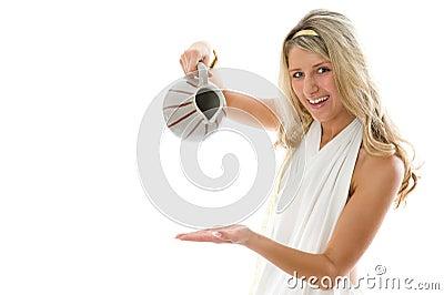 La giovane ragazza attraente versa il latte da una brocca