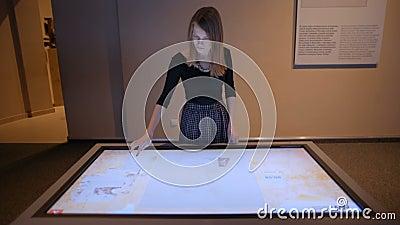 La giovane signora sta raccogliendo il puzzle sul touch screen con l'immagine antica dell'icona archivi video