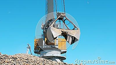 La grue jaune transporte des décombres dans un seau métallique Concept d'exploitation minière industrielle banque de vidéos