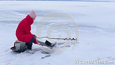 La jeune belle femme dans les bottes rouges de veste et de feutre s'assied sur la glace et pêche des poissons en trou avec la can clips vidéos