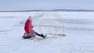 La jeune belle femme dans les bottes rouges de veste et de feutre s'assied sur la glace et pêche des poissons en trou avec la can banque de vidéos