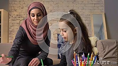 La jeune belle mère dans le hijab faisant des leçons de devoirs, petite fille choisit des crayons de couleur, dessine, le ` s d'e banque de vidéos