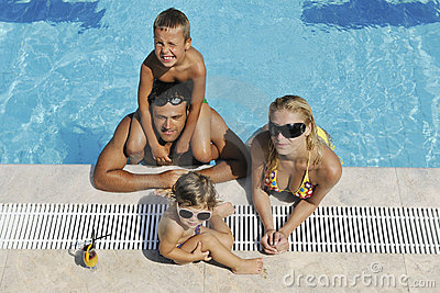 La jeune famille heureuse ont l amusement sur la piscine