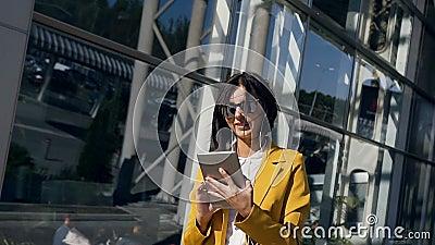 La jeune femme d'affaires dans un costume travaille sur la tablette près du centre en verre moderne d'affaires pendant une pause  banque de vidéos