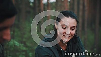 La jeune femme de brune dans le hoodie vert parle à l'ami masculin dans la forêt au pique-nique banque de vidéos