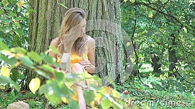 La jeune femme a fini le livre de lecture sous le tronc d'arbre épais 4K clips vidéos