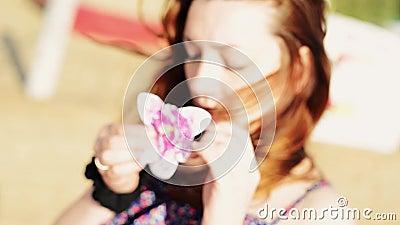 La jeune fille avec la fleur sur la plage regardent in camera Jour ensoleillé insousiant Les gens banque de vidéos