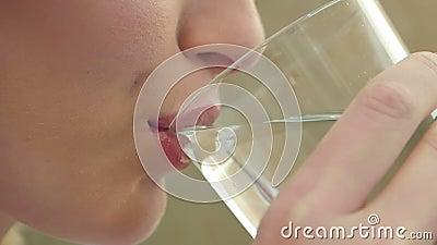 La jeune fille magnifique maintient sain en buvant un verre de l'eau à l'intérieur et le sourire banque de vidéos