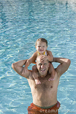 La jeune fille sur le père épaule dans la piscine