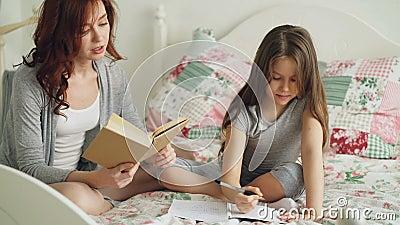 La jeune mère aide sa petite fille mignonne avec des devoirs pour l'école primaire Maman affectueuse lisant un livre et une fille banque de vidéos
